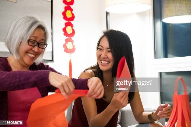 women enjoy preparing for chinese new year celebrations - 63 year old female stock pictures, royalty-free photos & images