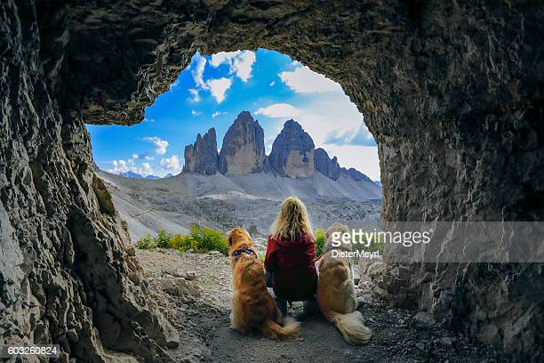 Women enjoy the view with dogs out of cave, Dolomites