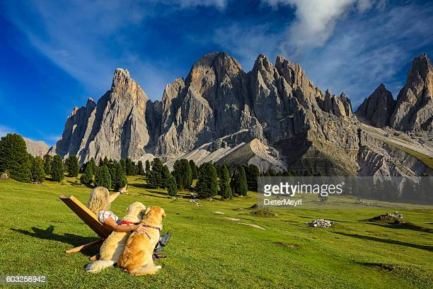 Women enjoy the view with her dogs, Geisler Gruppe, Alps