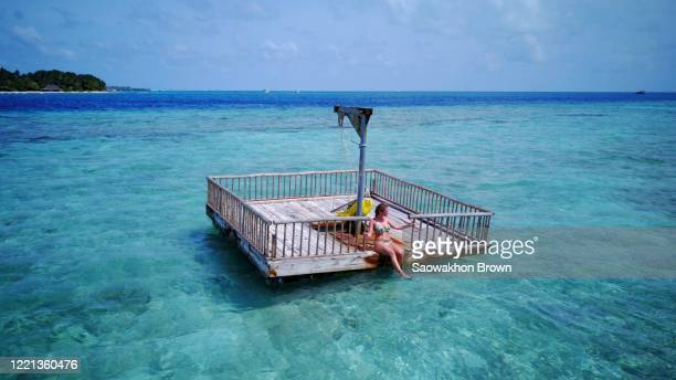 women enjoy vacation sitting on pontoon floating on clear water inn maldives - pontoon bridge stock pictures, royalty-free photos & images