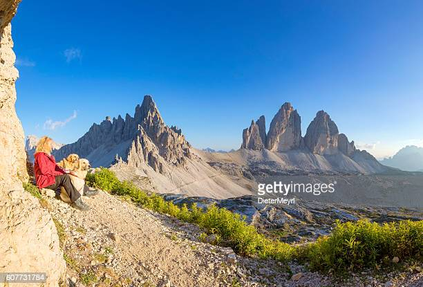 Women enjoy view with her dogs to Tre Cime, Dolomites