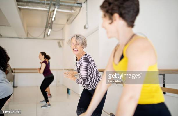 women enjoying a dance routine in fitness studio - mid adult women stock pictures, royalty-free photos & images