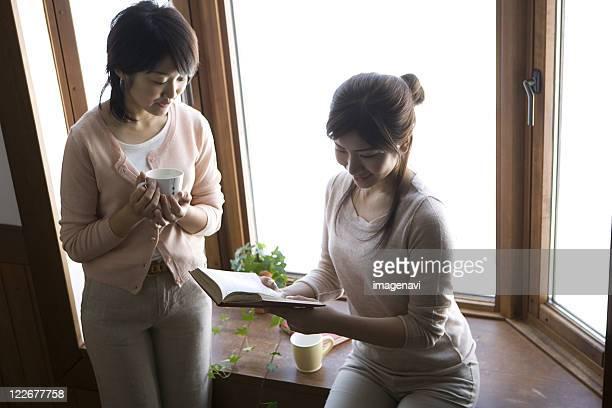 Women Enjoying Chatting by Window