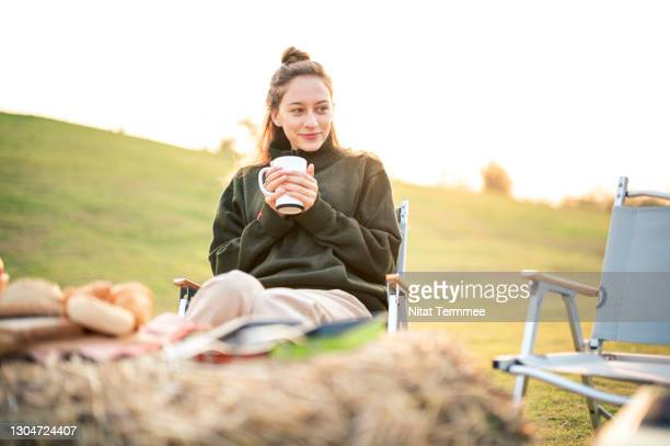 women enjoying coffee or hot drink while sitting on camping chair during sunrise. camping, simple, sustainable lifestyle. - キャンプ 1人 ストックフォトと画像
