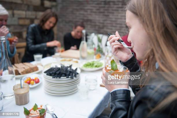 Women enjoying lunch outdoors, girl eating soup