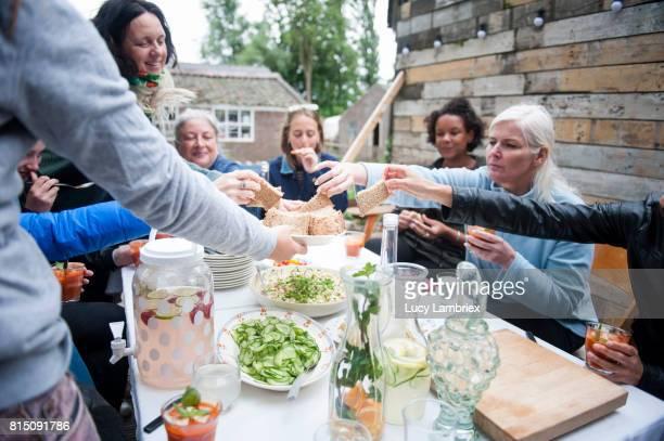 Women enjoying lunch outdoors, taking bread