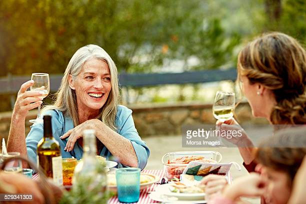 Women enjoying wine while having meal with family
