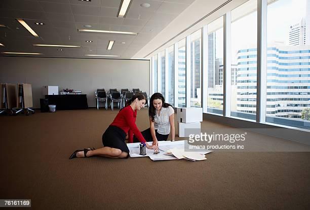 Women examining blueprints on floor