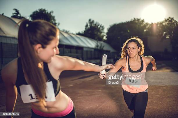 women exchanging relay baton on a sports race. - relay stock pictures, royalty-free photos & images
