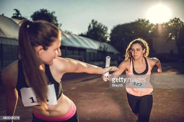 Donne lo scambio di staffetta in una gara sportiva.