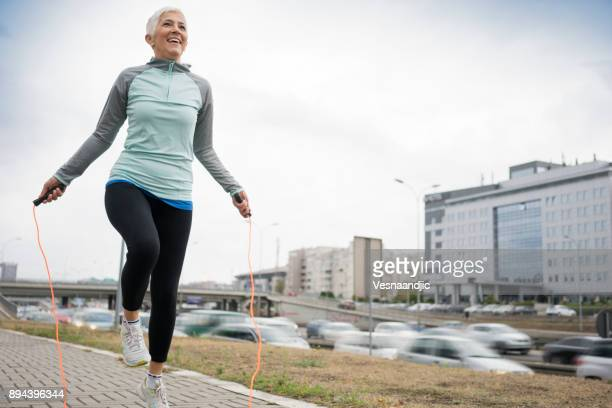 women exercise in city - 50 59 years stock pictures, royalty-free photos & images