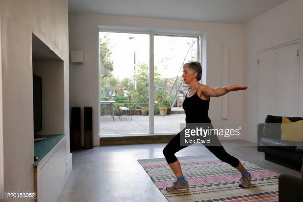 a women exercising from home in a large living room area. - girl power provérbio em inglês - fotografias e filmes do acervo