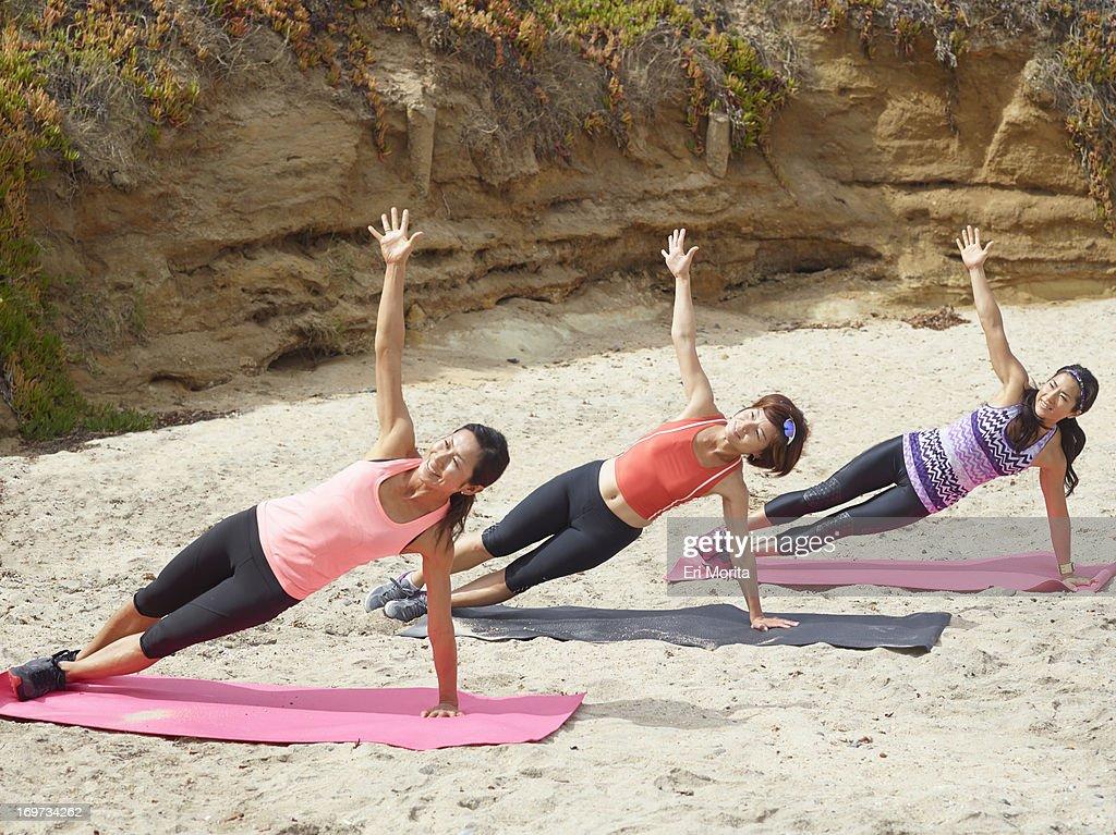 3 women exercising on beach : Stock Photo