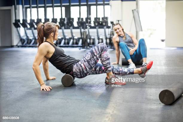 women exercising on foam rollers in gym - de rola imagens e fotografias de stock