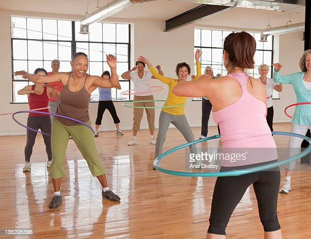 Women spinning plastic hoops in fitness class