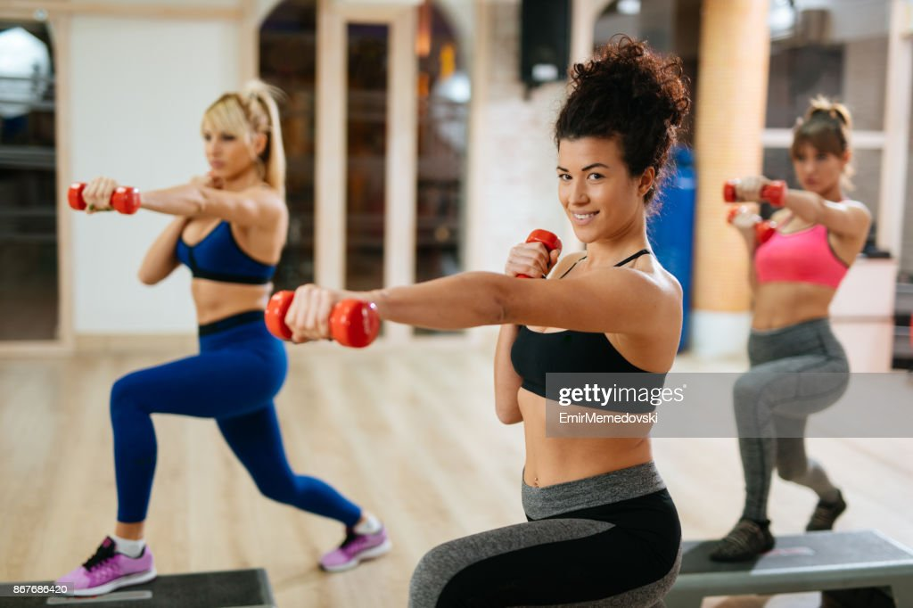 women exercising step aerobics with dumbbells at the gym stock photo