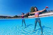 women exercising with dumbbells swimming pool