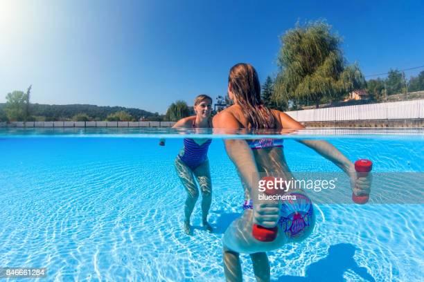 Mujeres haciendo ejercicio con pesas en la piscina