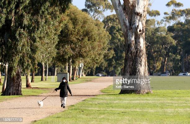 Women exercising with her dog is seen at Victoria Park on July 21, 2021 in Adelaide, Australia. South Australia is in lockdown after a cluster of...
