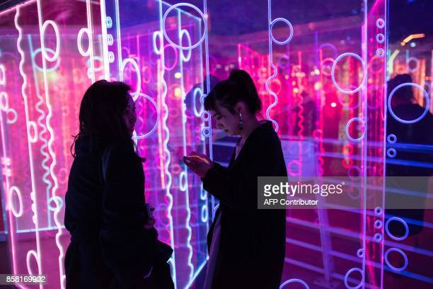 Women experience the illuminated art installation maze entitled 'Heofon' which features in the annual 'Light Night Leeds' festival of visual arts in...