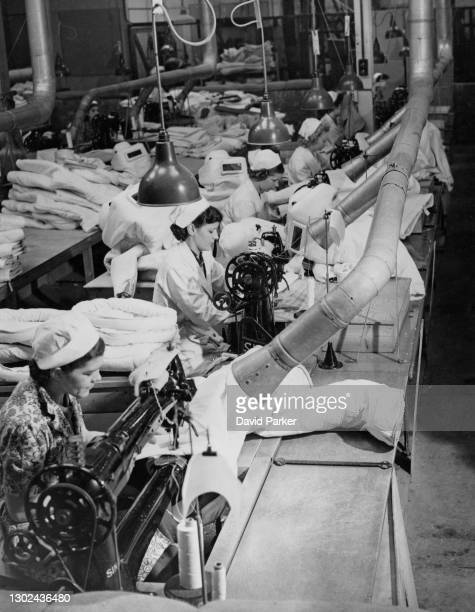 Women factory workers using Singer Sewing machines manufacture asbestos fire protection suits for the Royal Air Force and Fleet Air Arm fire fighting...