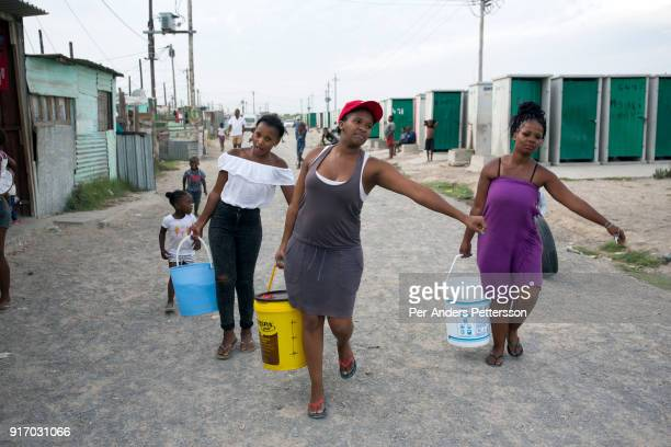 FEBRUARY 8 Women fetch water at a communal tap on February 8 2018 in Khayelitsha about 40 kilometers outside of Cape Town South Africa The city of...