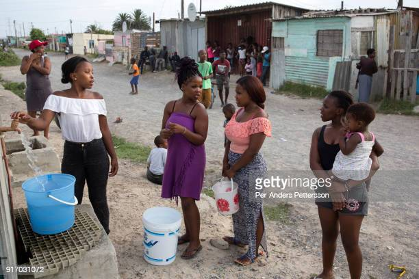Women fetch water at a communal tap on February 8 2018 in Khayelitsha about 40 kilometers outside of Cape Town South Africa The city of Cape Town is...