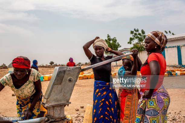 Women fetch water at the Minawao refugee camp near Gadala on March 3, 2020. - The camp was established in 2013 and hosts over 60,000 Nigerian...