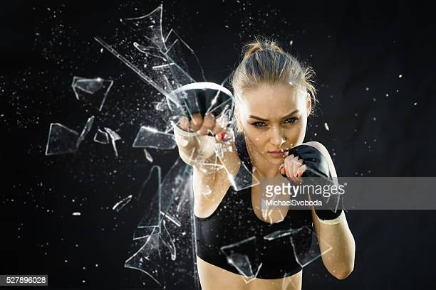 women fighter punching close up glass shattering - vernieling stockfoto's en -beelden