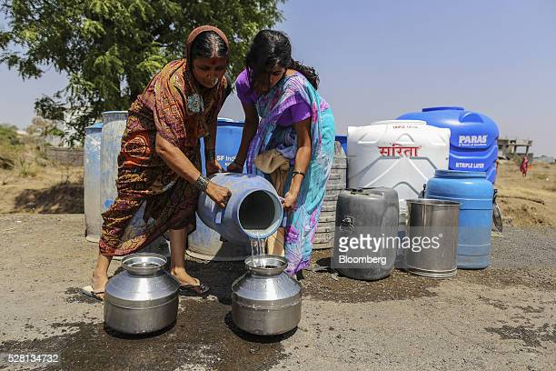 Women fill vessels with water from public drums at a village in Beed district Maharashtra India on Friday April 15 2016 Hundreds of millions of...