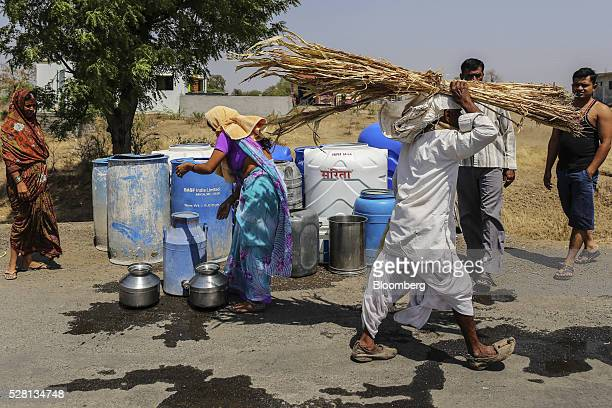 Women fill vessels with water from public drums at a village in Beed district, Maharashtra, India, on Friday, April 15, 2016. Hundreds of millions of...