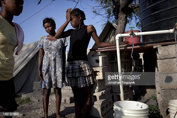 Women filling water buckets at a water station at one of the many displaced people camps in Port-au-Prince on January 2011 in Port-au-Prince, Haiti.