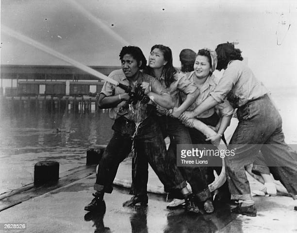 Women fire fighters during a training exercise at the Pearl Harbor Naval Shipyard during World War II circa 1941 From left to right they are...