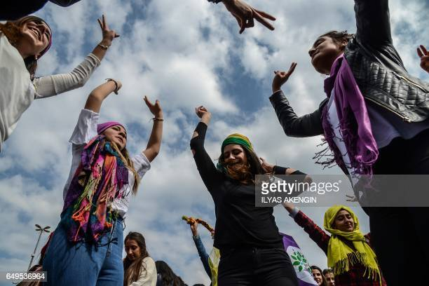 TOPSHOT Women flash victory signs during a demonstration as part of International Women's Day on March 8 2017 in Diyarbakir / AFP PHOTO / ILYAS...