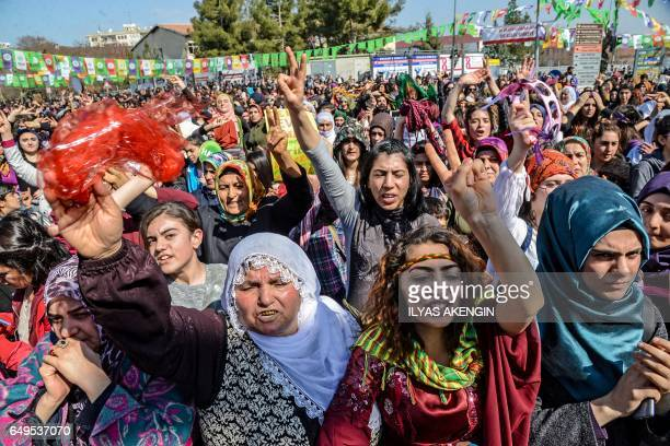 Women flash victory signs during a demonstration as part of International Women's Day on March 8 2017 in Diyarbakir / AFP PHOTO / ILYAS AKENGIN