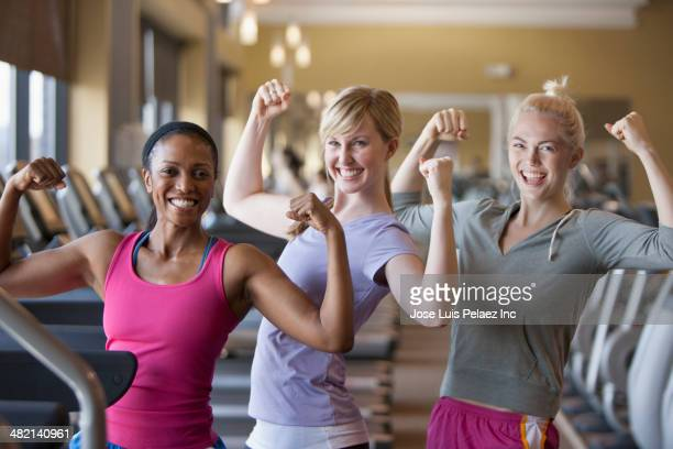 Women flexing muscles in gym