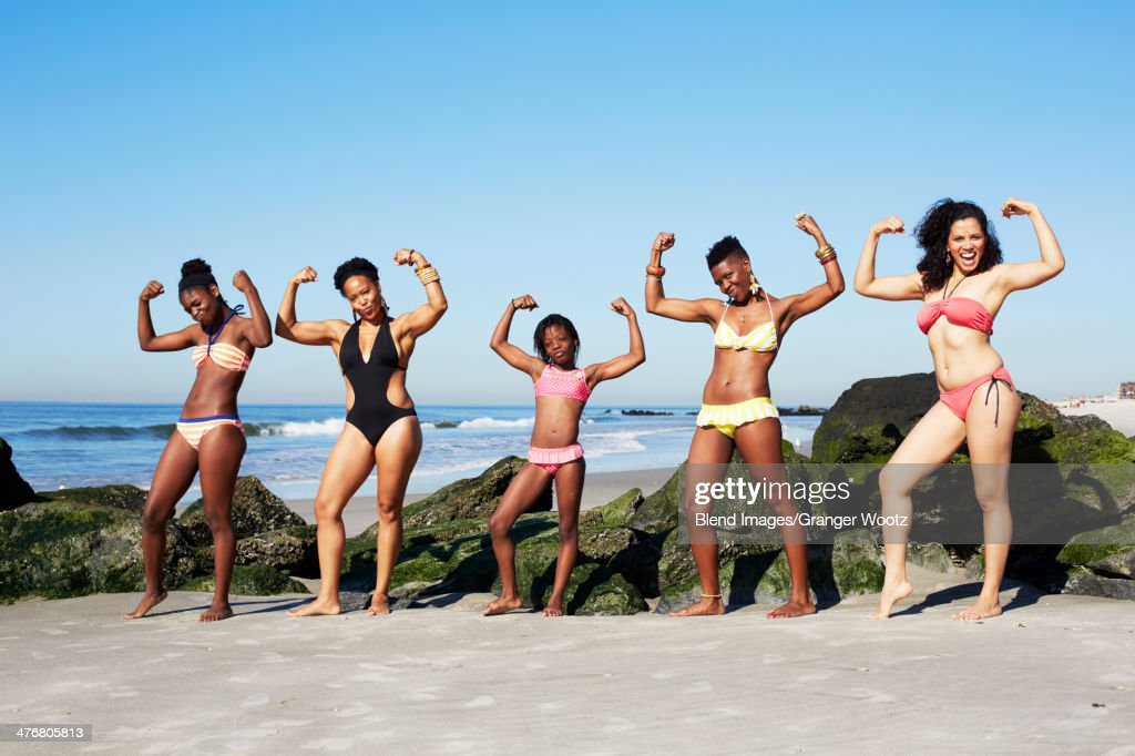 Women flexing muscles on beach : Stock Photo