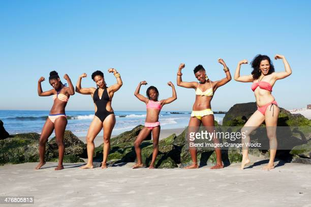 Women flexing muscles on beach