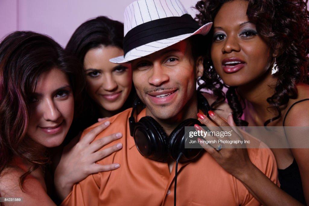 Women flirting with DJ in nightclub : Stock Photo