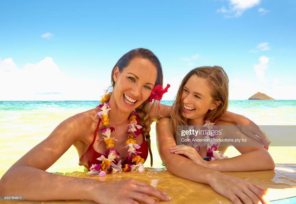 Women floating on surfboard in ocean : Foto stock