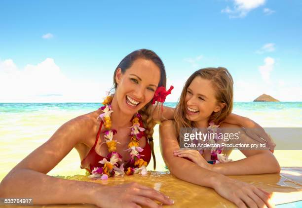 women floating on surfboard in ocean - lei day hawaii stock pictures, royalty-free photos & images
