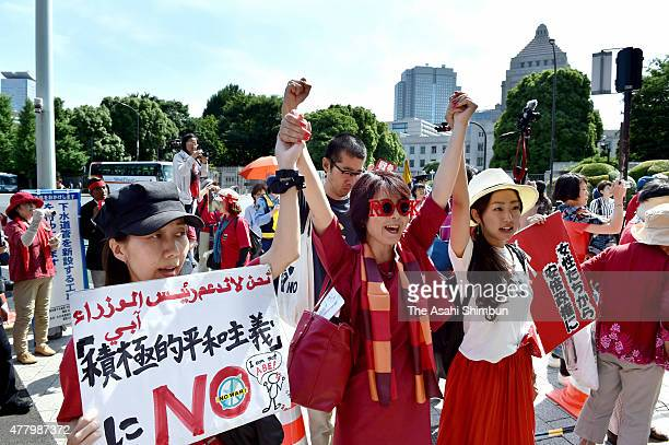 Women form a human chain around the Diet building to oppose the controversial security legislation during a rally on June 20 2015 in Tokyo Japan...