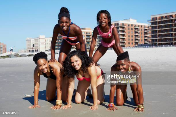 Women forming pyramid on beach