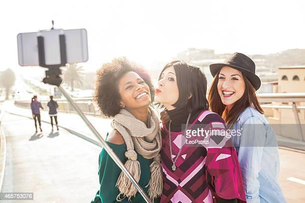 Women friend outdoor taking selfies with selfie stick