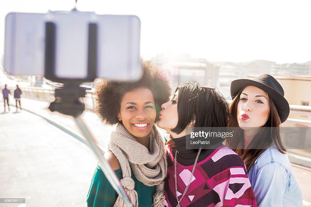Women friend outdoor taking selfies with selfie stick : Stock Photo