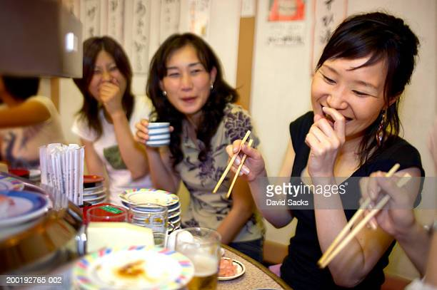 Women friends dining in restaurant, laughing
