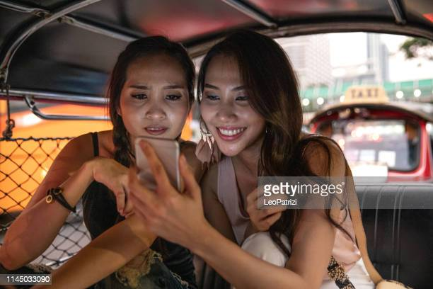 women friends discovering bangkok on board of a tuk tuk, thailand - rickshaw stock pictures, royalty-free photos & images