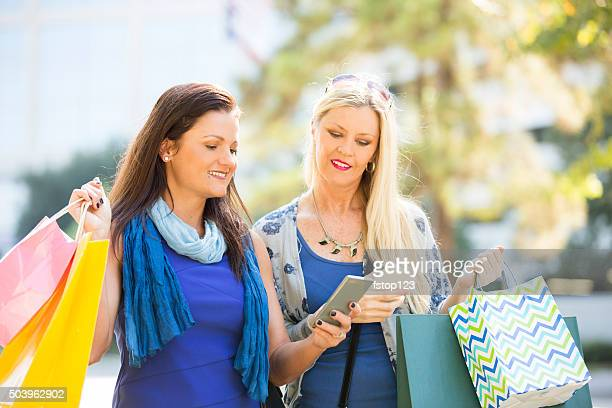 Women friends downtown with cell phones. City street. Shopping bags.