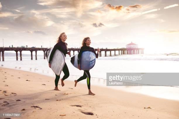 freundinnen gehen surfen - santa monica stock-fotos und bilder