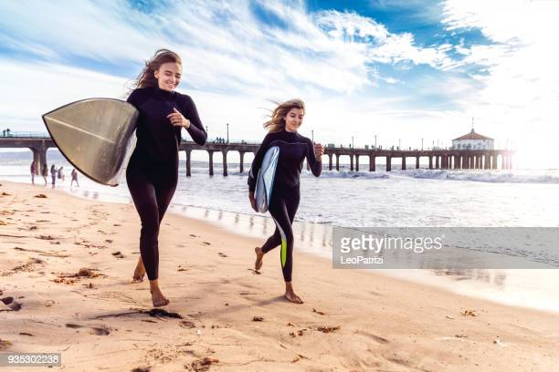 women friends going to surf in los angeles - california - santa monica los angeles foto e immagini stock